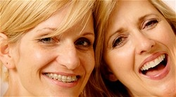 two woman smiling, one with braces